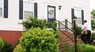 Door-to-Door Salesman Greets Homeowner Stock Footage