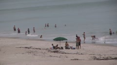 People on the beach playing in the ocean Stock Footage