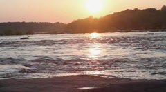 Caucasian couple holding hands and hugging on riverbank at sunset Stock Footage