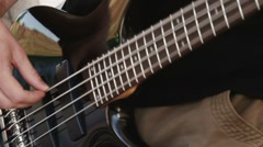 Man playing black bass guitar, fast zoom in Stock Footage