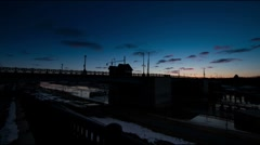 Sunrise time-lapse cloudscape with bridge and ice moving down river - stock footage