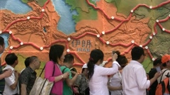 Chinese tourists walk past Iran map Stock Footage