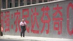 An old man seems lost in front of huge Chinese characters in Shanghai Stock Footage