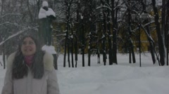 Teenage girl having fun with snow in a park Stock Footage