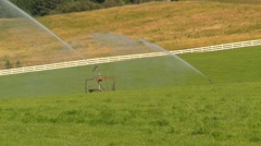 Agriculture, irrigation sprinklers and hay field, long shot Stock Footage