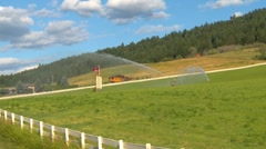 Agriculture, irrigation sprinklers and hay field, wide shot Stock Footage