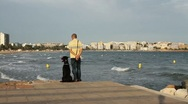 Man with his dog looking at the seashore Stock Footage