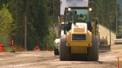 Construction highway building, #8 grader leveling dirt with dump truck Stock Footage