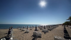 Many parasols and deckchairs standing on beach Stock Footage