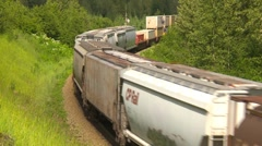 Stock Video Footage of railroad, freight train through frame around bend wide, medium shot