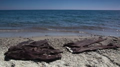 Brown suit lay on sand near water Stock Footage