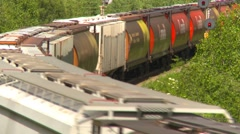 Stock Video Footage of railroad, freight train through frame around bend wide, long shot