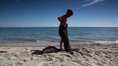 Boy tries to put on pants suit, jacket layed near on beach - stock footage