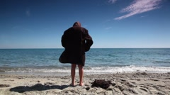 Boy in mens suit jacket stand back to camera on beach Stock Footage