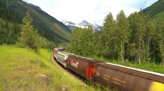 Stock Video Footage of railroad, freight train through frame around bend wide, mountain valley