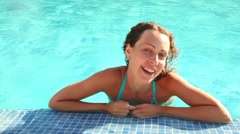 Woman laying in wavy pool water Stock Footage