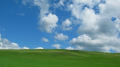 Green hill with grass under cloudy sky - timelapse Stock Footage