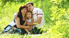 Smilling family in the grass loking at camera - stock footage