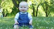 Baby sits in grass and gently nods head Stock Footage