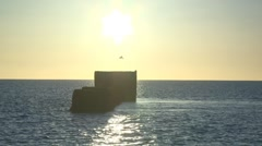 Time lapse sun rise over sea outfall Stock Footage