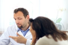 Male doctor telling bad news to female patient NTSC - stock footage