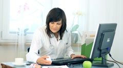 Female doctor working on computer and checking medications HD Stock Footage