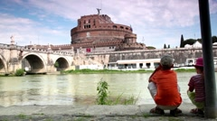 Two children sitting and look at the Sant Angelo Bridge and Sant Angelo Castel Stock Footage