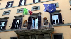 Wall of the building with balcony it is fitted flags of Italy and the EU Stock Footage