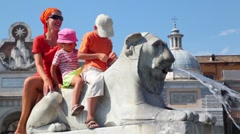 Mother and her kids sit on statue of lion near Flaminio obelisk Stock Footage