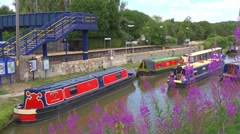 Narrowboat cruising past Heyford wharf, Oxfordshire.  Railway station behind. Stock Footage