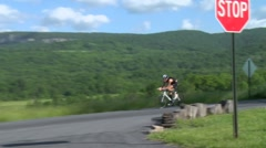 Triathlon biking by older male biker takes a turn on a country road 2 Stock Footage