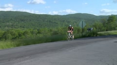 Triathlon biking by older male biker takes a turn on a country road Stock Footage