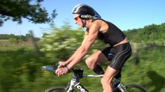 Triathlon biking by older male biker riding from right to left Stock Footage