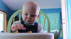 Baby boy eats bread in booster chair Stock Footage