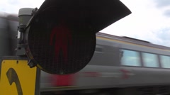 Pedestrians do not cross - red flashing man as a train passes 4:2:2 Stock Footage