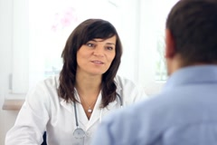 Female doctor talking with male patient - stock footage