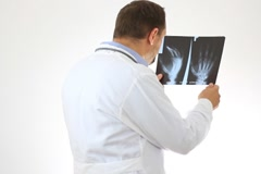 Male doctor looking at xray of human hand, isolated - stock footage