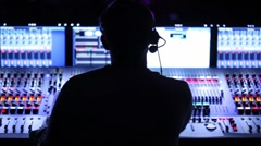 Silhouette of sound producer, which sits at mixer panel - stock footage