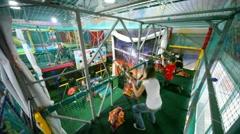 Children shoot from an air gun balls in playroom Stock Footage