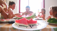 Sliced watermelon on plate and family around table eat it - stock footage