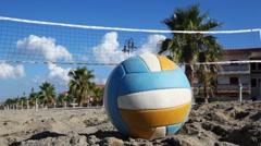 Ball lies on sand under volleyball net at beach Stock Footage