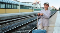 Boy with travel bag stands and smiles on train station near railway lines Stock Footage