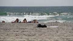 3 girls on a beach watching boogie boarders in the distance Stock Footage