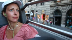 Beautiful woman rides on open top floor of bus at streets Stock Footage