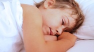 Stock Video Footage of Little girl openes her eyes and awake on pillow