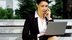 Young business woman sitting on bench, working with laptop and talking cell Stock Footage