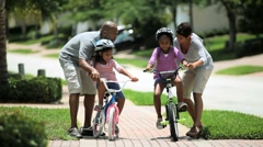 Little African American Girls Learning to Ride a Bike Stock Footage