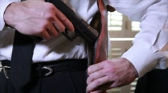 Stock Video Footage of detective putting gun in holster
