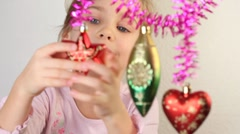 Little girl play with christmas-tree decoration, which hang. Stock Footage