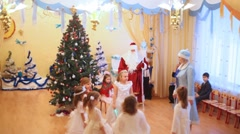 Girls in snowflakes fancy-dress act nearby christmas-tree Stock Footage